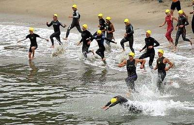 The first wave of triathletes hit the surf at Seacliff State Beach for the start of the 28th annual Sandman Triathlon on Aug. 4, 2013. (Dan Coyro -- Santa Cruz Sentinel file)